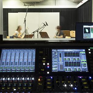 Tonstudio mit Mischpult. Hinter einer Scheibe sitzen zwei Musikerinnen mit Instrumenten im Aufnahmeraum.