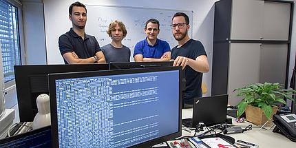 Ein großer Computerbildschirm mit vielen Zeichen ist im Vordergrund zu sehen. Dahinter stehen vier Männer.