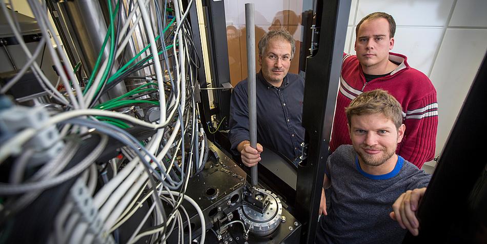 Drei Forscher vor einem Mikroskop.
