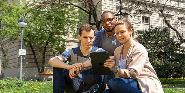 3 Studierende blicken auf ein Tablet. Bildquelle: Lunghammer – TU Graz