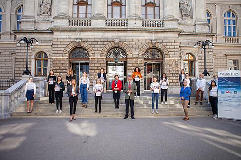 Gruppe aus Schülerinnen und Erwachsenen auf einem Stiegenaufgang vor Gebäudeeingang
