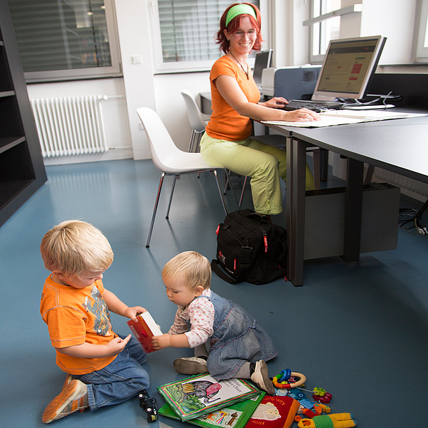 Woman sitting in front of a computer, two children playing next to her. Photo source: Lunghammer - TU Graz
