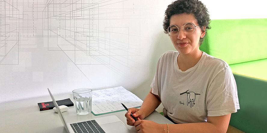 Junge Frau sitzt an einem Schreibtisch mit Laptop, Schreibunterlagen, Buch und Wasserglas.