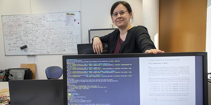 Eine junge Frau steht hinter einem Computerbildschirm und hat eine Hand auf ihn gelegt. Der Computerbildschirm ist blau und voll mit weißer Schrift.