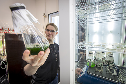 A woman stands in front of a kind of refrigerator and holds a glass flask with green liquid in the camera.