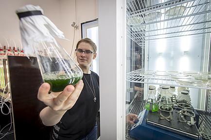 Eine Frau steht vor einer Art Kühlschrank und hält einen Glaskolben mit grüner Flüssigkeit in die Kamera.