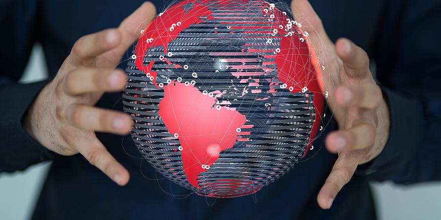 Zwei Hände halten eine stilisierte Weltkugel mit rot eingefärbten Kontinenten.