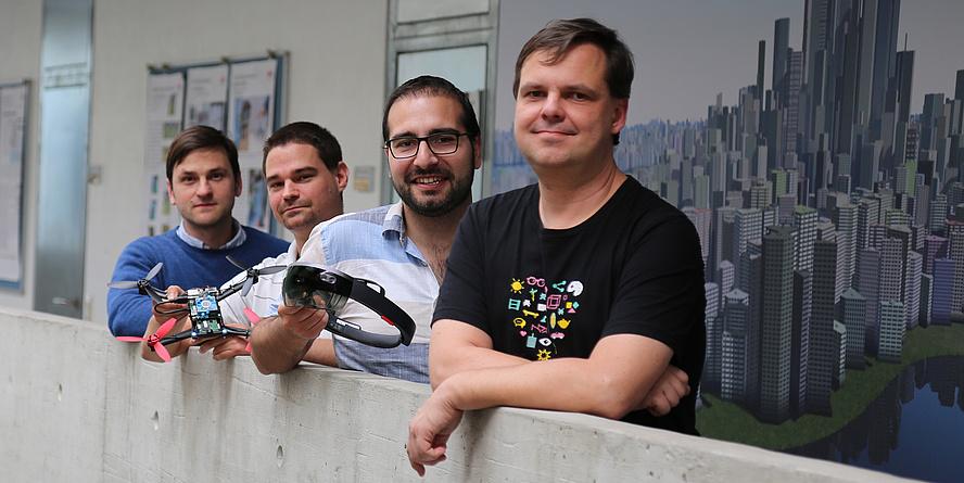 Vier Männer stehen und lehnen sich an einer Betonmauer an.
