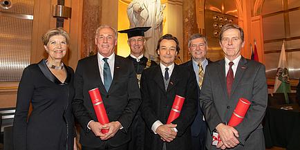 Eine Frau und fünf Männer stehen nebeneinander in festlicher Kleidung, drei Männer halten eine rote Urkundenrolle in Händen