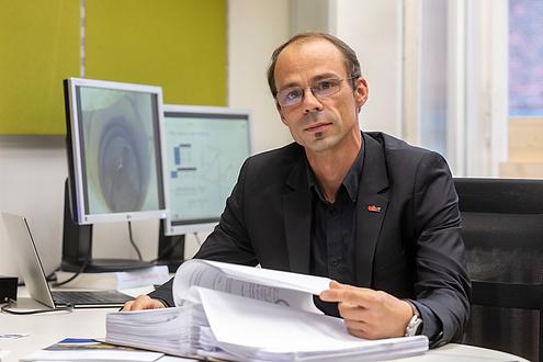 TU Graz researcher leafs through a file folder