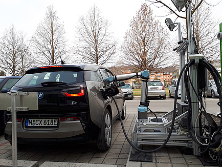 A blue electric vehicle is charged by the robot. The arm of the robot is plugged into the vehicle socket.