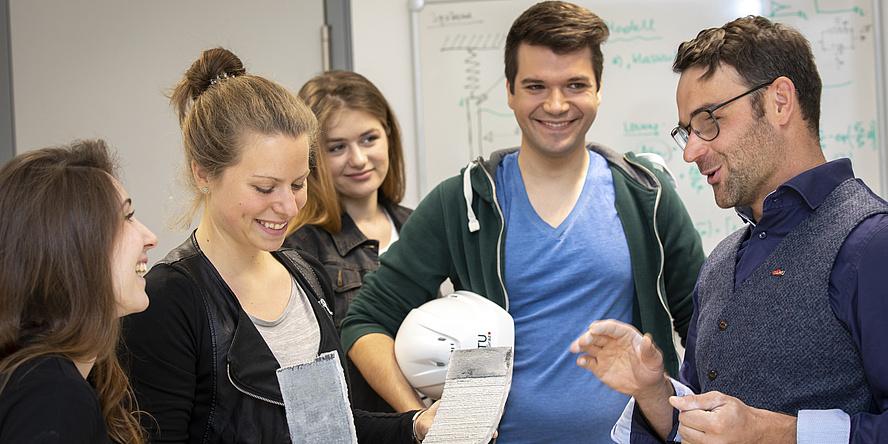 Drei Studierende hören einem Vortragenden zu. Ein Mann hält einen weißen Bauhelm in den Händen und eine Frau ein Stück Beton.