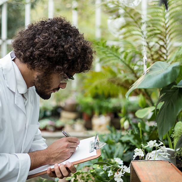 Mann mit Labormantel und Schutzbrille zwischen Pflanzen.