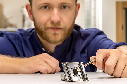 TU Graz researcher holds a one-cent coin with tweezers, in front of it a small sensor