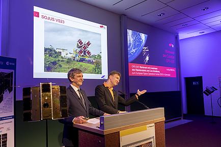 Zwei Männer sprechen vor Publikum; im Hintergrund Powerpoint Folien