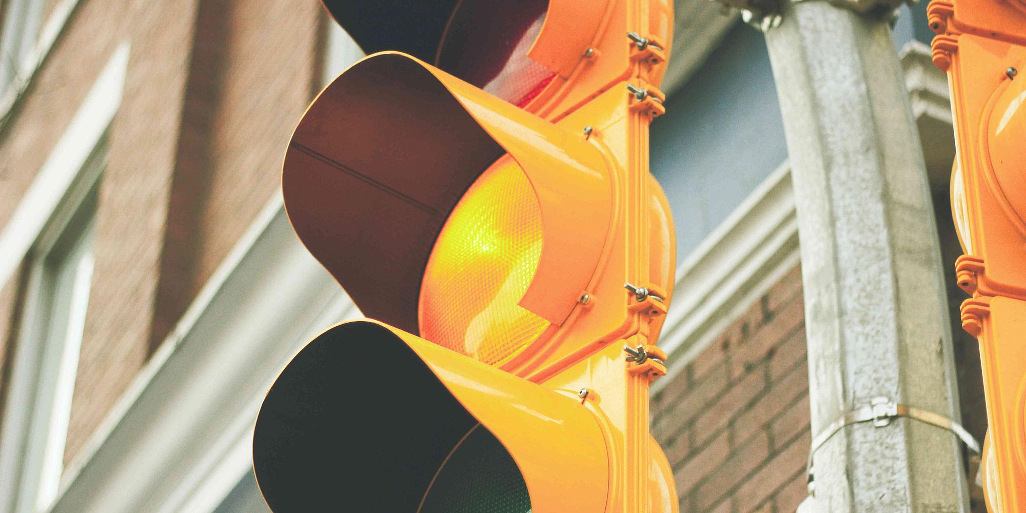 Ausschnitt einer gelben Ampel vor einem Backsteinhaus