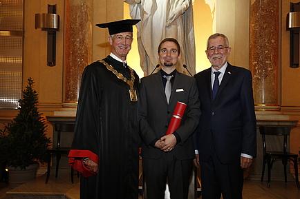 Drei Männer in festlichem Gewand, jener in der Mitte hält eine rote Diplomrolle in der Hand.
