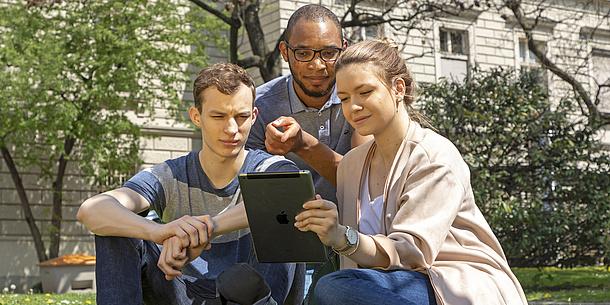 Zwei Studenten stehen vor einem Gebäude der TU Graz und blicken auf ein Tablet.