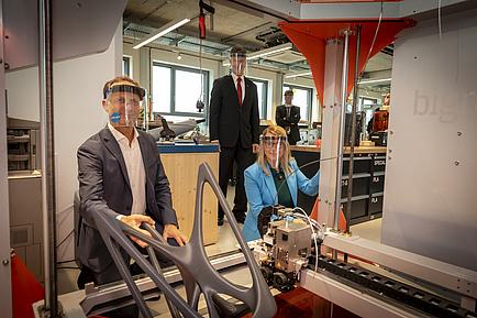 Eine FRau und drei Herren vor einer Maschine in einem Labor