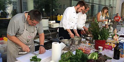 Ein Mann mit einem grauen Hemd ist über einen Tisch gebeugt. Er trägt eine weiße Schürze und schneidet mit einem Messer Grünzeug.