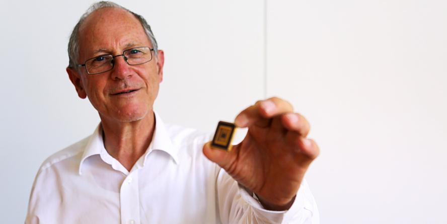 Ein Mann mit grauen Haaren hält eine schwarze Platte mit goldenen Streifen in die Kamera. Er trägt ein weißes Hemd.