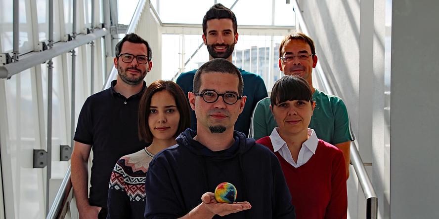 Mehrere Personen: In der Mitte steht ein Mann mit kurzen Haaren und einer Brille. In der Hand hält er einen kleinen Ball, der wie eine Erdkugel aussieht. Dahinter stehen zwei Frauen mit ebenfalls dunklen Haaren. Dahinter stehen drei Männer.