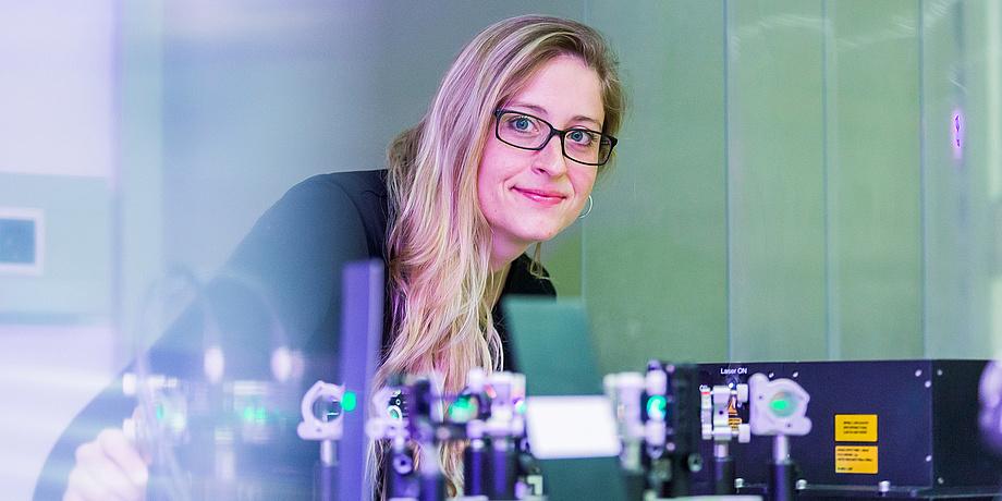 Blonde Frau mit Brille lehnt über technischer Apparatur