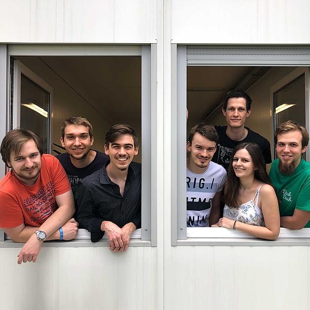 7 junge Leute lachen aus einem Fenster.