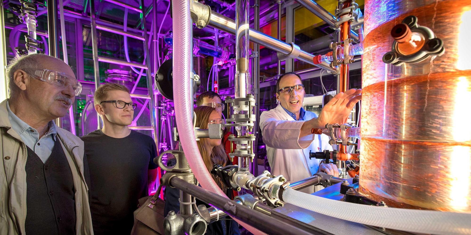 Forscher erklärt Besucher eine Maschine.