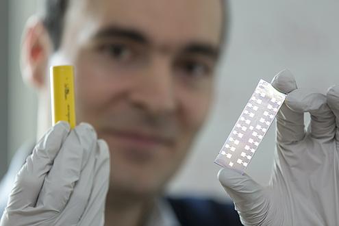 Ilie Hanzu mit einer Batterie und einer Solarzelle in den Händen.