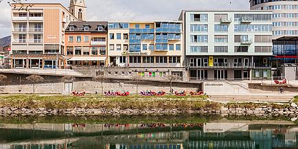 Zu sehen ist ein Stadtbild von Villach, die Draufassade und links davon der Kirchturm.