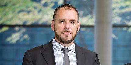 Paolo Falcaro mit Anzug und Krawatte vor einem grünblauen Hintergrund