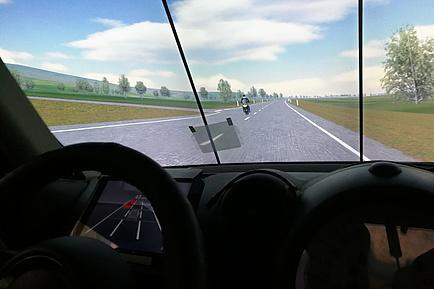 Cockpitperspektive, hinter der Windschutzscheibe ist eine virtuelle Landschaft, auf der Freilandstraße fährt ein gelbes Motorrad, das das Auto offensichtlich gerade überholte. Am Instrumentenbrett hinter dem Lenkrad wird die Straße und das Motorrad als roter Punkt angezeigt.