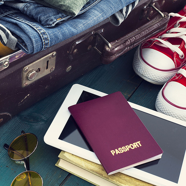 Open suitcase packed with personal things, passport, books and shoes. Photo source: sebra - Fotolia.com