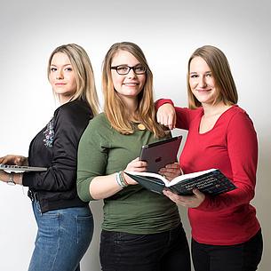 [Translate to Englisch:] 3 Studentinnen mit Notebook, Tablet und Lehrbuch in den Händen. Bildquelle: Kanizaj – TU Graz