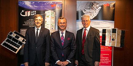 Drei Herren in Anzügen stehen vor zwei Roll Ups der TU Graz und werden flankiert von zwei Satelliten-Modellen