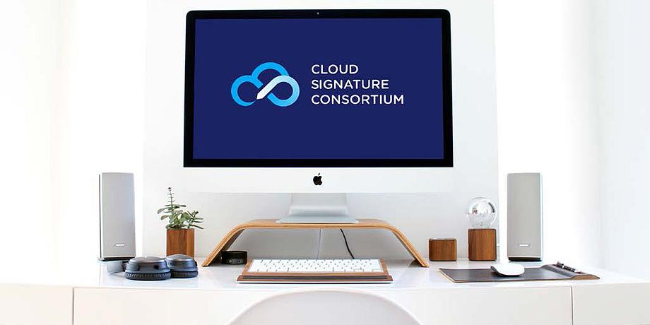 das Bild zeigt einen Computerarbeitsplatz mit einem Bildschirm und einer Tastatur sowie zahlreichen Büroutensilien. Am Bildschirm ist das Logo des Cloud Signature Consortiums zu sehen.