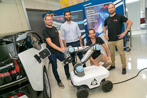 Vier Männer vor einer Plattform auf Räder mit Roboterarm