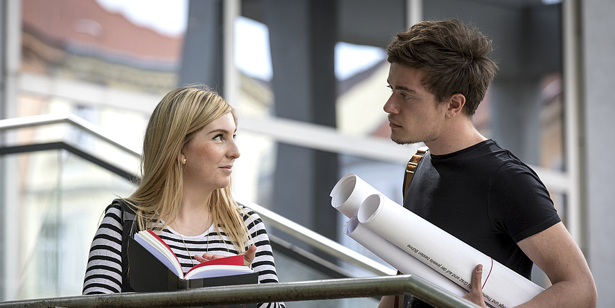 Eine Frau und ein Mann mit Schreibblock und großen Papierrollen.