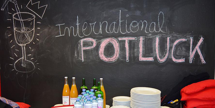 """Angerichtetes Buffet mit Getränken und leeren Tellern vor einer Tafel mit der Aufschrift """"International Potluck""""."""