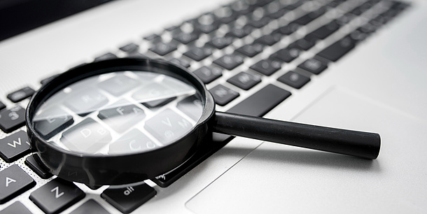 A magnifying glass lying on a computer keyboard.