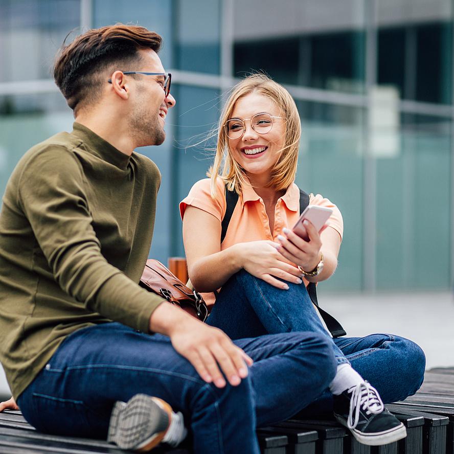 Zwei Jugendliche sitzen auf einer Bank und sehen sich an.