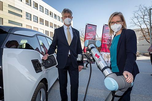 Mann und Frau neben einem E-Auto mit automatischem E-Laderoboter