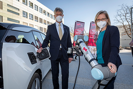 Man and woman next to an e-car with automatic e-charging robot