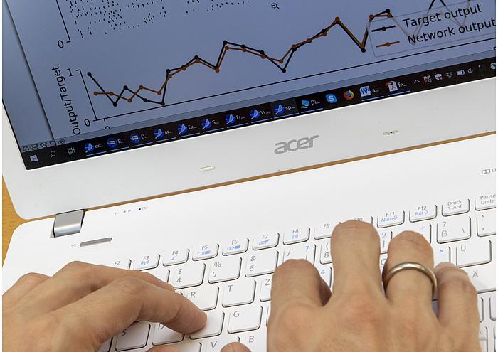 Ein weißer Laptop, auf dem zwei Hände liegen. Auf einem Finger ist ein Ring.