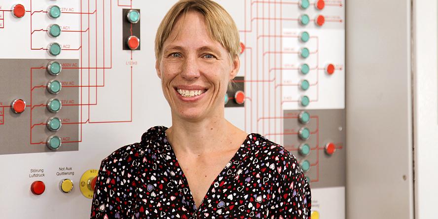 Frau vor einer Wand mit roten und grünen Knöpfen, die mit Linien verbunden sind.