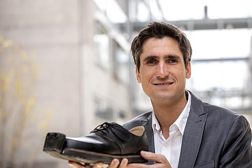 Mann mit Schuh in der Hand