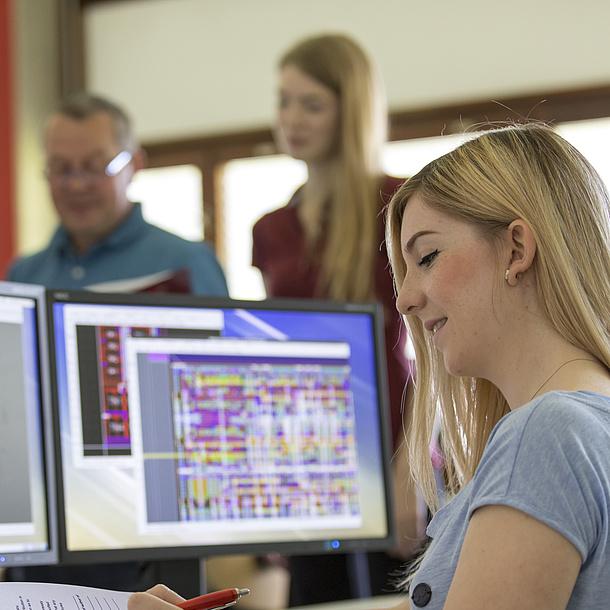 Ein Studentin sitzt vor zwei Bildschirmen, auf denen man Schaltkreise sieht.