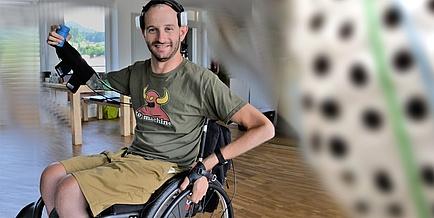 Ein junger Mann sitz im Rollstuhl und hält den rechten Arm in die Höhe, mit dem er eine Dose hält.
