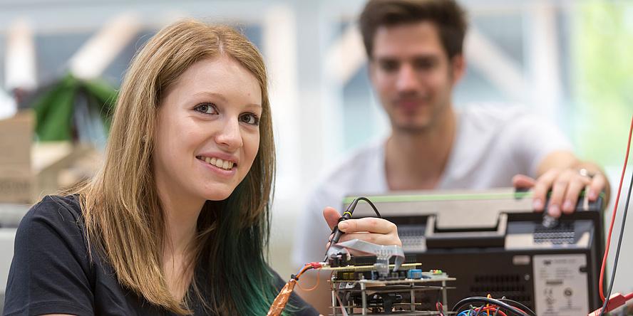 Eine junge Frau arbeitet an einem elektrischen gerät und blickt dabei lächelnd in die Kamera. Im Hintergrund sieht ihr ein junger Mann dabei zu.